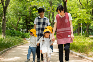 公園を散歩する保育士と園児の写真素材 [FYI04267707]