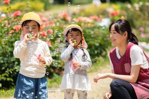 公園で遊ぶ保育士と園児の写真素材 [FYI04267731]