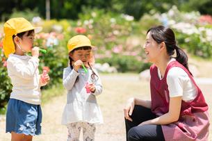 公園で遊ぶ保育士と園児の写真素材 [FYI04267735]