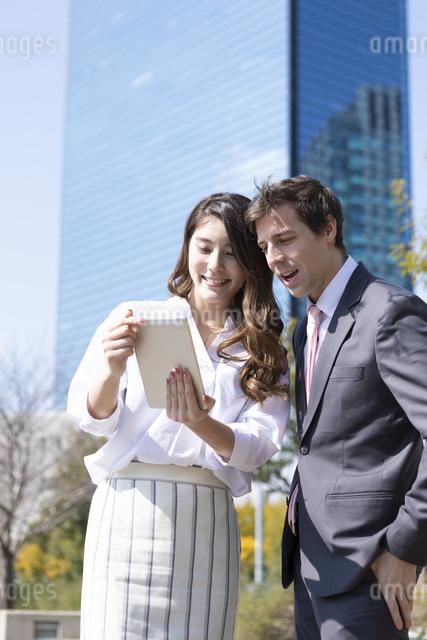 タブレットを見るビジネスマンとビジネスウーマンの写真素材 [FYI04268785]