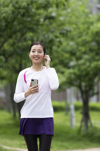 音楽を聴きながら歩く女性の写真素材 [FYI04269382]