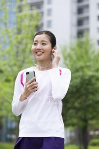 音楽を聴きながら歩く女性の写真素材 [FYI04269387]