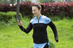 音楽を聴きながら走る女性の写真素材 [FYI04269389]