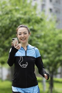 音楽を聴きながら走る女性の写真素材 [FYI04269390]
