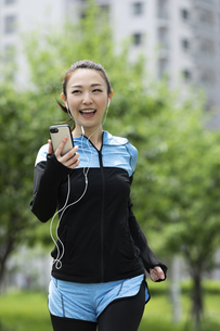 音楽を聴きながら走る女性の写真素材 [FYI04269391]