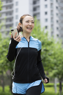 音楽を聴きながら走る女性の写真素材 [FYI04269393]