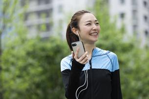 音楽を聴きながら歩く女性の写真素材 [FYI04269397]