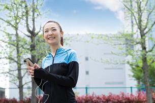 音楽を聴きながら歩く女性の写真素材 [FYI04269398]