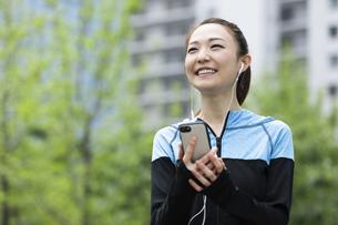 音楽を聴きながら歩く女性の写真素材 [FYI04269399]
