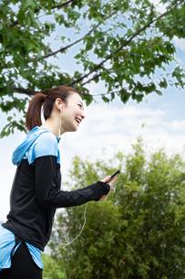 音楽を聴きながら歩く女性の写真素材 [FYI04269401]