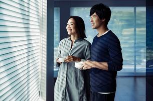 朝日を浴びながらコーヒーを飲む夫婦の写真素材 [FYI04269606]