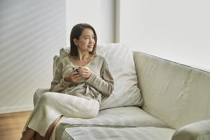 ソファでスマホを持ちながら外を見る30代女性の写真素材 [FYI04269608]