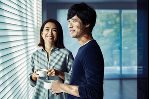 朝日を浴びながらコーヒーを飲む夫婦の写真素材 [FYI04269610]