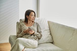 ソファでスマホを持ちながら外を見る30代女性の写真素材 [FYI04269611]