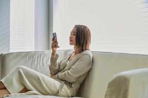 ソファでスマホを見る30代女性の写真素材 [FYI04269614]