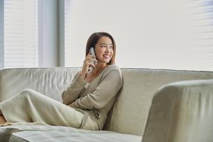 ソファでスマホで電話する30代女性の写真素材 [FYI04269615]