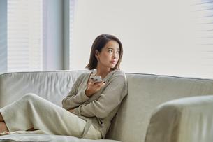 ソファでスマホを持ちながら外を見る30代女性の写真素材 [FYI04269617]