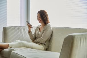 ソファでスマホを見る30代女性の写真素材 [FYI04269618]