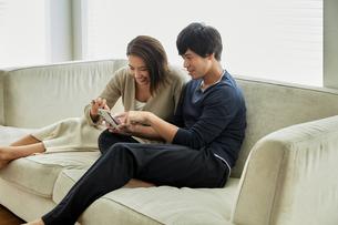 ソファでスマホを見て笑う夫婦の写真素材 [FYI04269619]