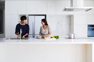 キッチンで料理する夫婦の写真素材 [FYI04269622]