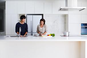 キッチンで料理する夫婦の写真素材 [FYI04269623]