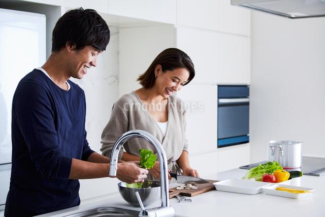 キッチンで料理する夫婦の写真素材 [FYI04269624]