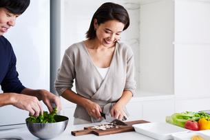 キッチンで料理する夫婦の写真素材 [FYI04269626]
