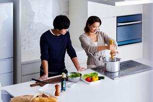 キッチンで料理する夫婦の写真素材 [FYI04269629]