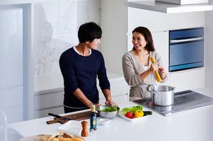 キッチンで料理する夫婦の写真素材 [FYI04269631]