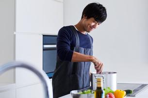 キッチンで料理する男性の写真素材 [FYI04269632]