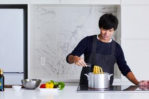 キッチンで料理する男性の写真素材 [FYI04269633]