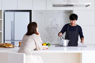 キッチンで料理する男性と眺める女性の写真素材 [FYI04269634]