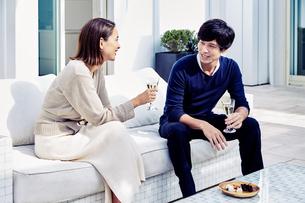 バルコニーでワインを飲みながら寛ぐ夫婦の写真素材 [FYI04269638]
