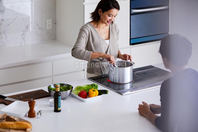 キッチンで料理する女性と眺める男性の写真素材 [FYI04269640]