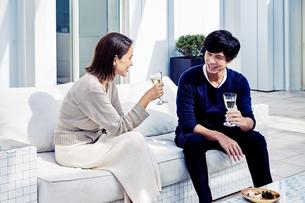 バルコニーでワインを飲みながら寛ぐ夫婦の写真素材 [FYI04269641]