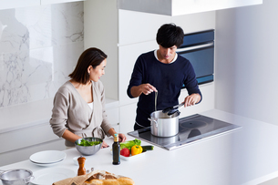 キッチンで料理する夫婦の写真素材 [FYI04269642]
