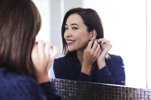 鏡の前でピアスをつける30代女性の写真素材 [FYI04269644]