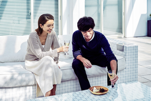 バルコニーでワインを飲みながら寛ぐ夫婦の写真素材 [FYI04269645]