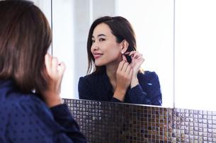 鏡の前でピアスをつける30代女性の写真素材 [FYI04269646]
