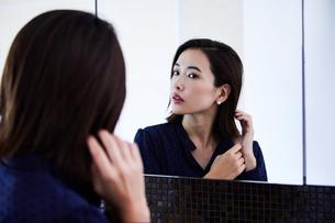 鏡の前でピアスをつける30代女性の写真素材 [FYI04269647]