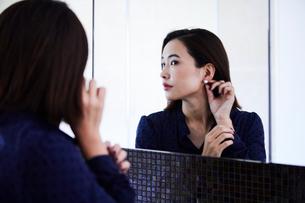鏡の前でピアスをつける30代女性の写真素材 [FYI04269648]