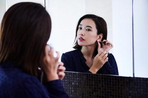 鏡の前でピアスをつける30代女性の写真素材 [FYI04269649]