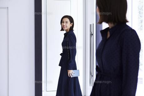 玄関の鏡の前で身だしなみチェックする女性の写真素材 [FYI04269650]