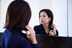 鏡の前でピアスをつける30代女性の写真素材 [FYI04269651]