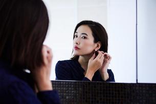 鏡の前でピアスをつける30代女性の写真素材 [FYI04269652]