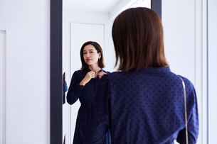 玄関の鏡の前で身だしなみチェックする女性の写真素材 [FYI04269653]