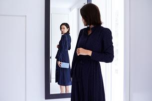 玄関の鏡の前で身だしなみチェックする女性の写真素材 [FYI04269654]
