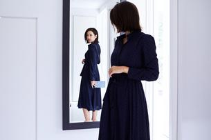 玄関の鏡の前で身だしなみチェックする女性の写真素材 [FYI04269655]