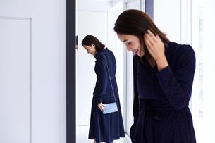 玄関の鏡の前で身だしなみチェックする女性の写真素材 [FYI04269656]