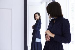 玄関の鏡の前で身だしなみチェックする女性の写真素材 [FYI04269657]